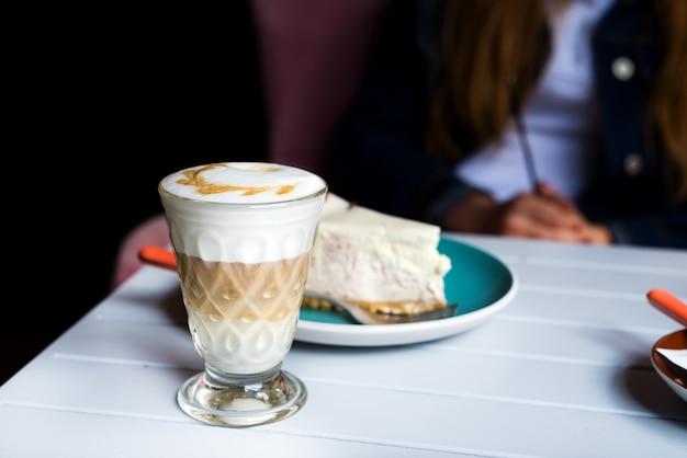 Bicchiere di latte macchiato con schiuma di latte ricca nella caffetteria