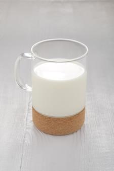 Bicchiere di latte sul tavolo da cucina di legno bianco