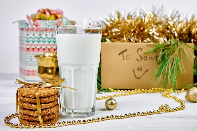 Bicchiere di natale con latte e biscotti per babbo natale sul tavolo