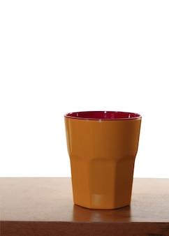 Bicchiere di plastica arancione brillante isolato su uno spazio bianco