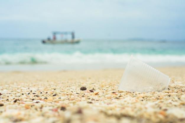 Bicchiere di plastica nel riciclaggio della spiaggia