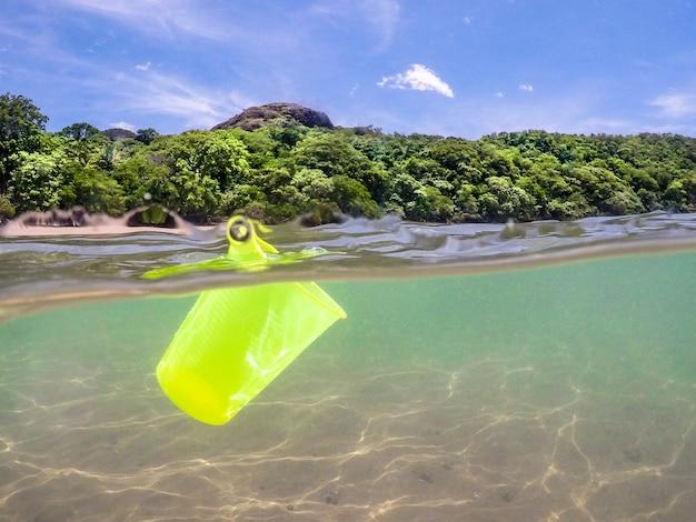 Bicchiere di plastica nell'oceano, riciclaggio