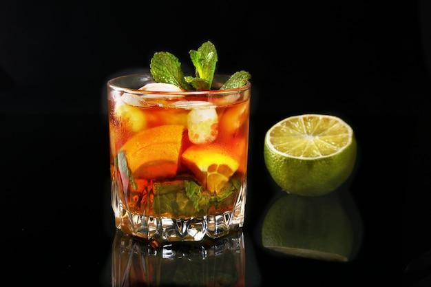 Bicchiere di rum scuro cocktail con lime, arancio, cubetti di ghiaccio e foglie di menta su sfondo nero a specchio.