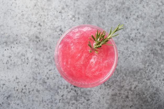 Bicchiere di spumante rosato con glitter commestibili luccicanti che guarniscono rosmarino su grigio. avvicinamento.