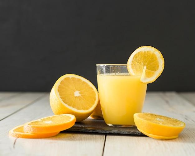 Bicchiere di succo d'arancia e fette di frutta su ardesia