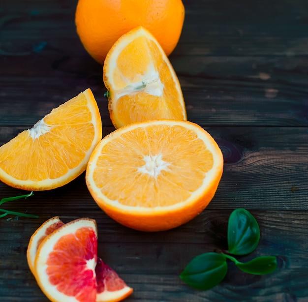 Bicchiere di succo d'arancia e un gruppo di arance sul bordo scuro