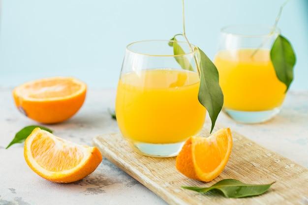 Bicchiere di succo d'arancia fresco con gruppo di arance