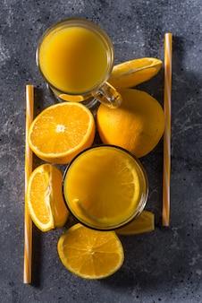 Bicchiere di succo d'arancia fresco, frutta e fette d'arancia mature
