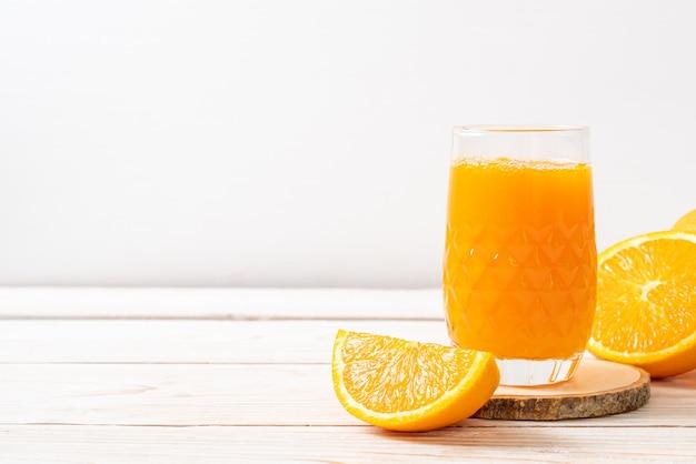 Bicchiere di succo d'arancia fresco su legno