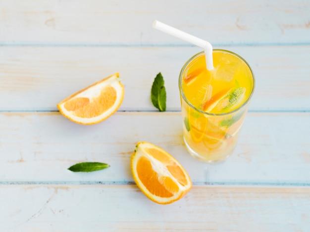 Bicchiere di succo d'arancia ghiacciato con fette e paglia