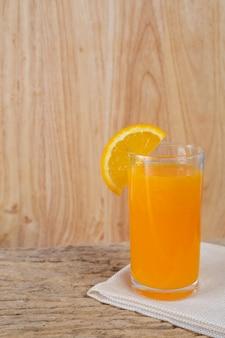 Bicchiere di succo d'arancia posto su legno.
