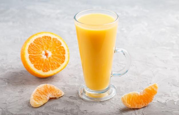 Bicchiere di succo d'arancia su uno sfondo grigio cemento