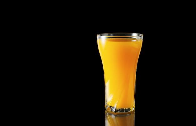 Bicchiere di succo d'arancia su uno sfondo nero