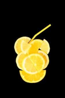Bicchiere di succo di agrumi fatto di fette di arancia e limone con cannuccia cocktail isolato su sfondo nero.