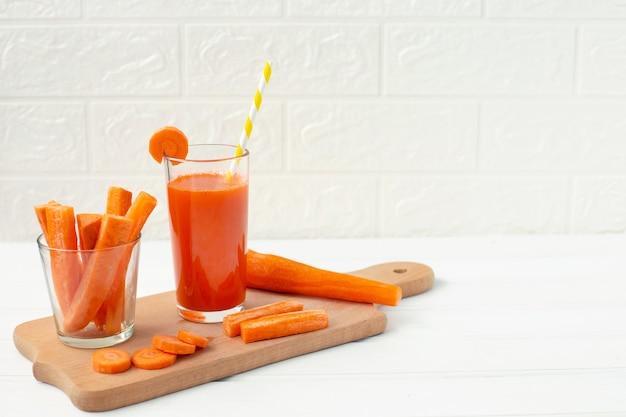 Bicchiere di succo di carota e carota fresca sul tagliere