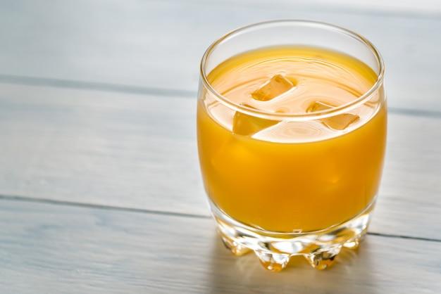 Bicchiere di succo di mango sul tavolo di legno
