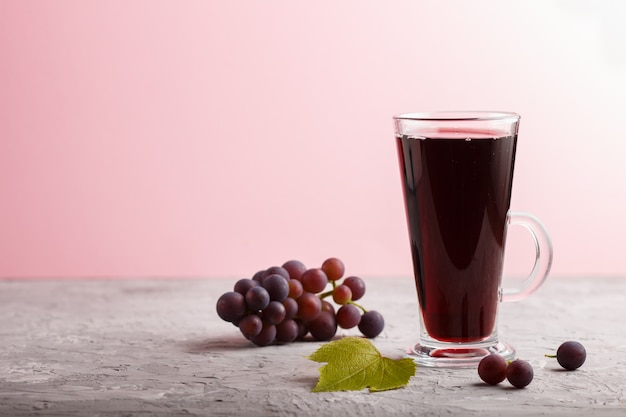 Bicchiere di succo di uva rossa su uno sfondo grigio e rosa. vista laterale