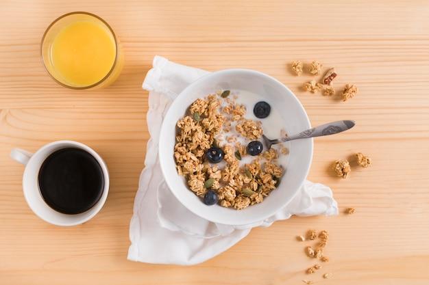 Bicchiere di succo; tè e farina d'avena sana sulla scrivania in legno