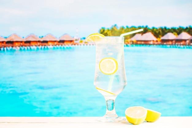 Bicchiere di succosa bevanda al limone con agrumi paglia e affettati
