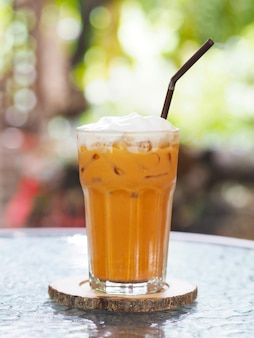 Bicchiere di tè al latte tailandese con panna montata sulla cima e paglia al caffè.