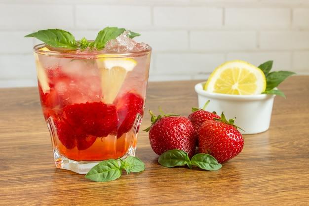 Bicchiere di tè freddo con menta, fragola, limone, sul tavolo
