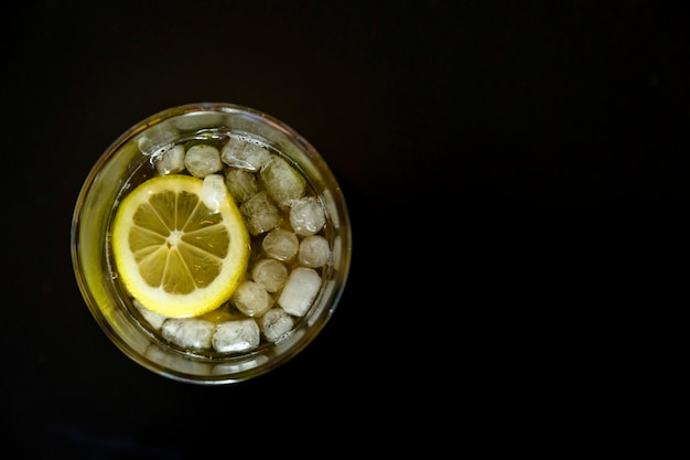 Bicchiere di tè freddo ghiacciato con fetta di limone sopra lo sfondo nero