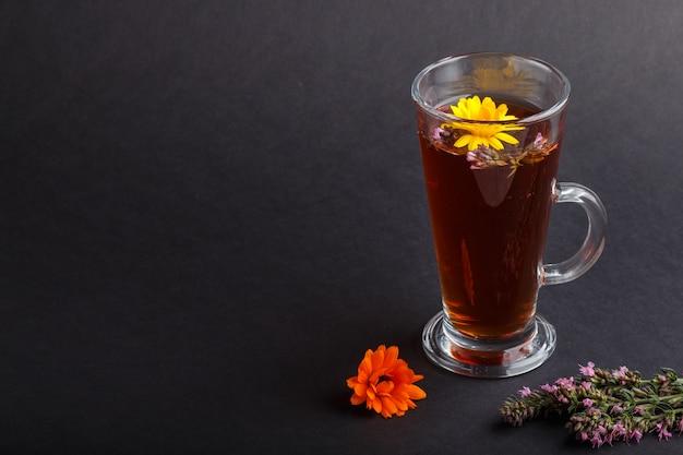 Bicchiere di tisana con calendula e issopo su sfondo nero. vista laterale, copia spazio.
