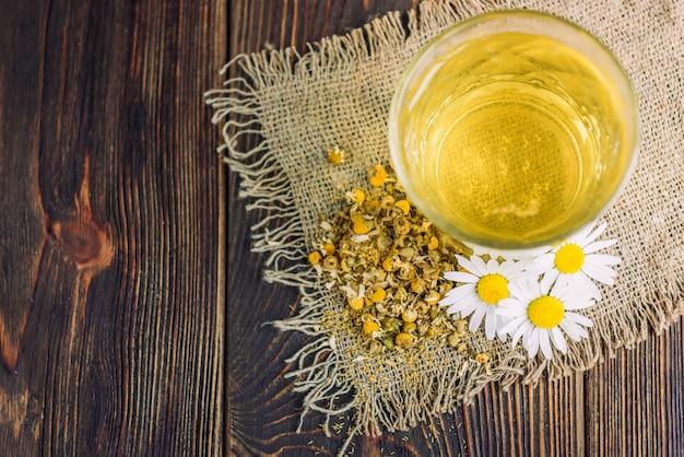 Bicchiere di tisana con fiori di camomilla su fondo di legno scuro.