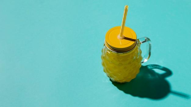 Bicchiere di vetro con coperchio giallo e paglia