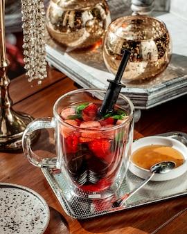 Bicchiere di vetro di frutti di bosco cocktail con fragole lampone e menta