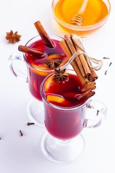 Bicchiere di vin brulé caldo con spezie e miele su sfondo bianco