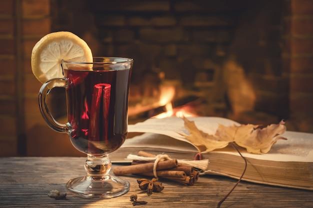 Bicchiere di vin brulè, spezie, un libro su un tavolo in una sala accogliente con caminetto
