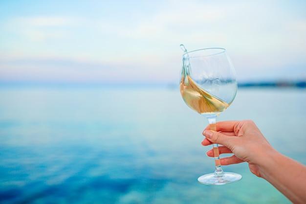 Bicchiere di vino bianco sulla spiaggia tropicale sul tramonto