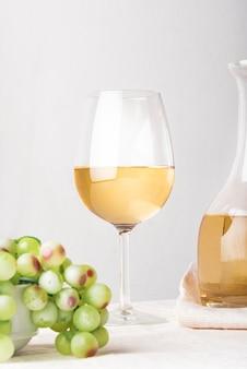 Bicchiere di vino con il primo piano verde dell'uva