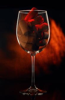 Bicchiere di vino con tappi su sfondo nero
