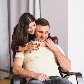 Bicchiere di vino della holding della giovane donna a disposizione che abbraccia il suo ragazzo che si siede sulla poltrona