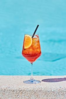 Bicchiere di vino di cocktail freddo aperol spritz contro acqua turchese a bordo piscina