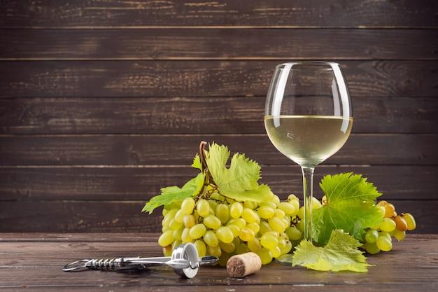 Bicchiere di vino e grappolo d'uva sulla tavola di legno