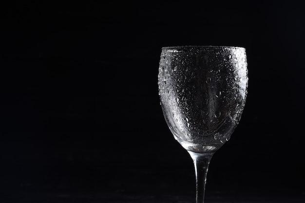Bicchiere di vino in bianco e nero su fondo nero con riflessi e gocce d'acqua