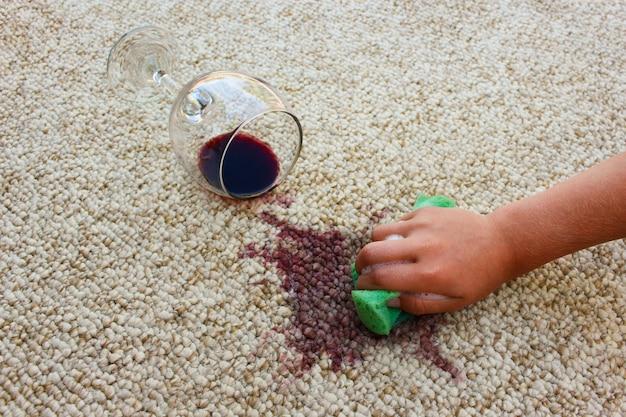 Bicchiere di vino rosso cadde sul tappeto, vino versato sul tappeto. la mano femminile pulisce il tappeto con una spugna e un detergente.