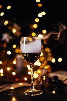 Bicchiere di vino rosso club di fumo. sfondo bokeh. natale, capodanno o san valentino.