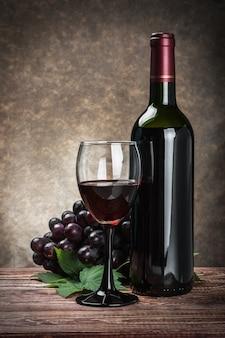 Bicchiere di vino rosso con bottiglia e uva