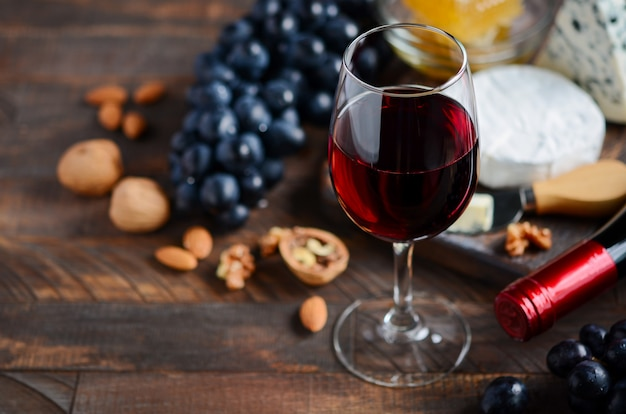 Bicchiere di vino rosso con formaggio, uva, miele e noci su un tavolo di legno