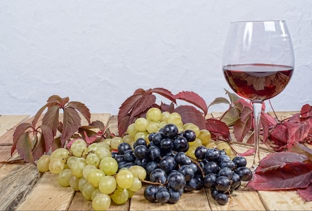 Bicchiere di vino rosso con molti grappoli d'uva