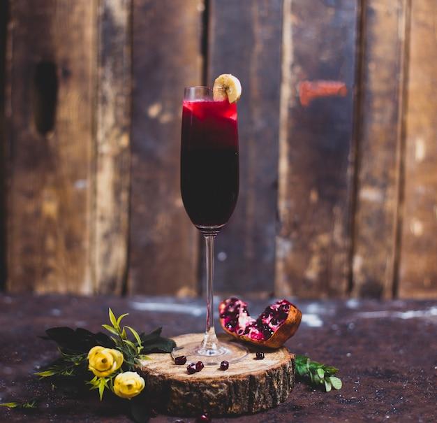 Bicchiere di vino rosso con una fetta di banana su un pezzo di legno con granato. sfondo rustico