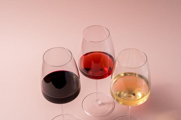 Bicchiere di vino rosso e bicchiere di vino rosato e bicchiere di vino bianco su sfondo rosa.