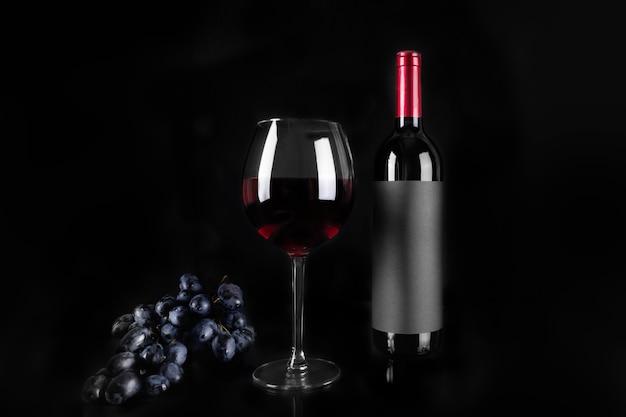 Bicchiere di vino rosso e bottiglia e grappolo d'uva