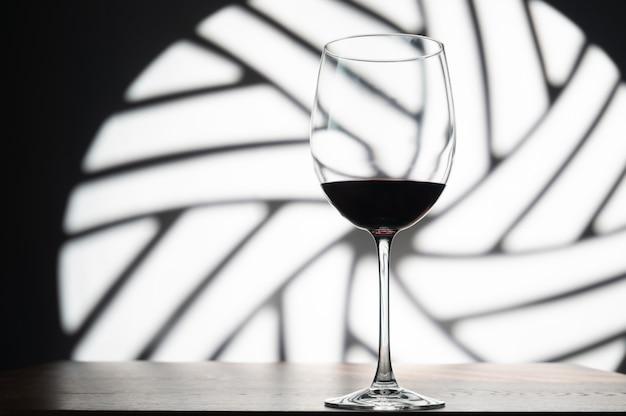 Bicchiere di vino rosso sullo spazio di una finestra rotonda decorativa