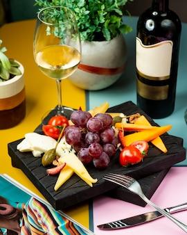 Bicchiere di vino servito con uva, formaggio e pomodoro