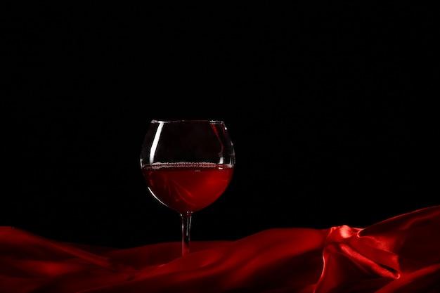 Bicchiere di vino su seta rossa con fondo scuro